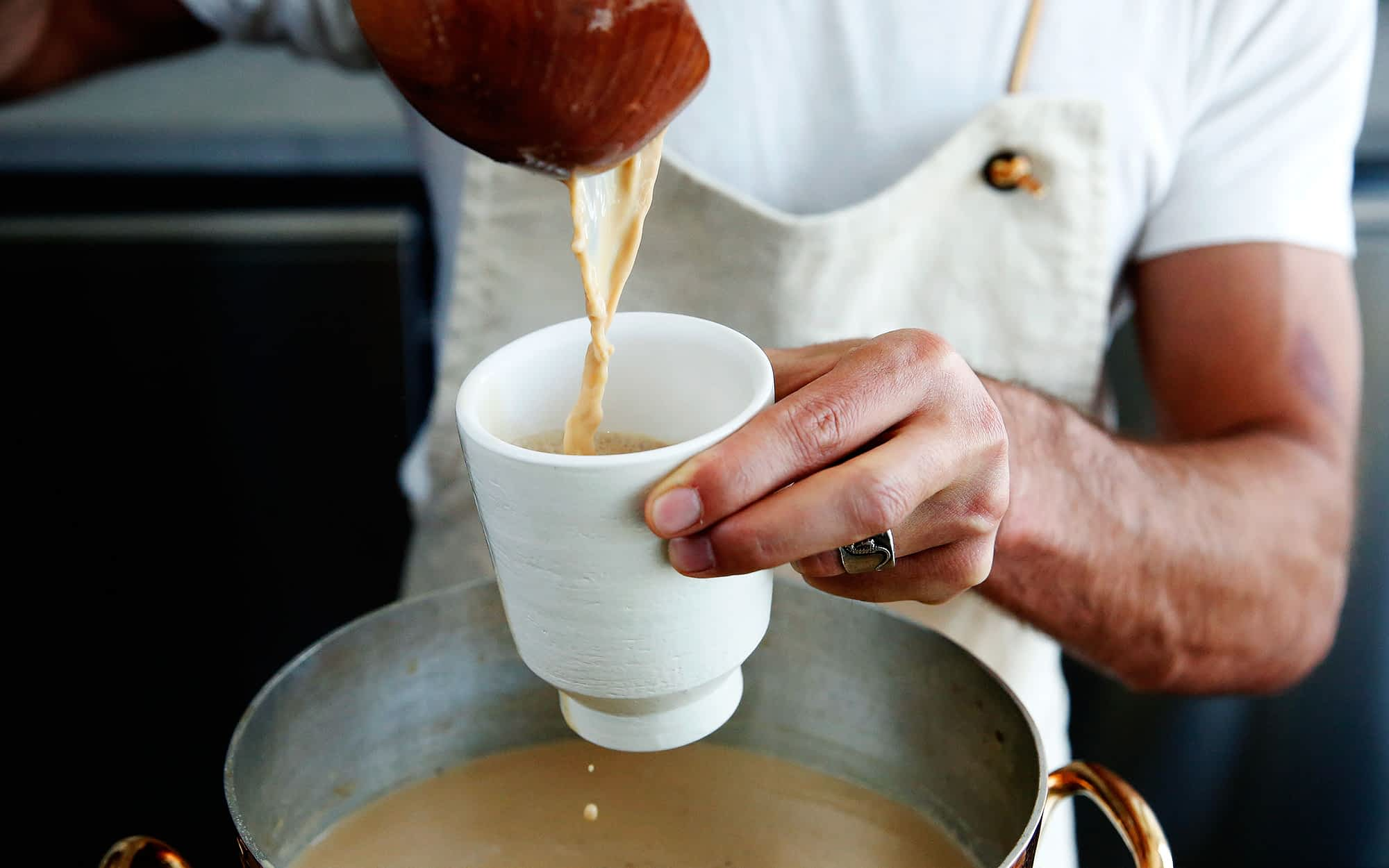 A server prepares a cup of chai